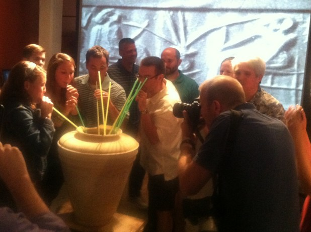 People gathered around a large vessel drinking from long straws.