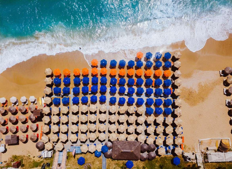 Aerial view of beach with sun umbrellas.