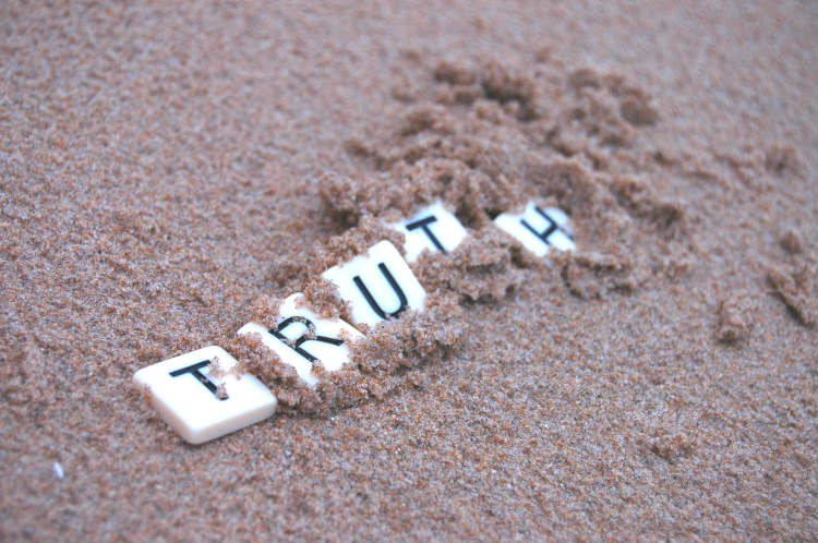 Letter tiles spelling 'truth' being covered up by sand.