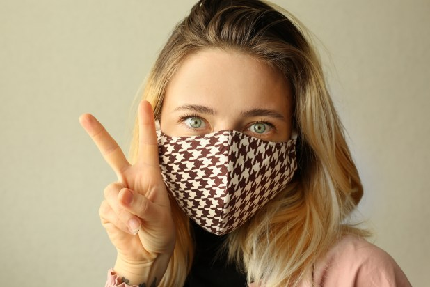 A woman wearing a chequered reusable cloth mask.