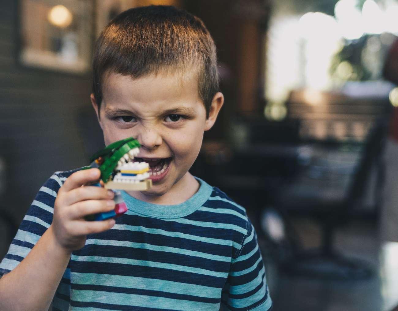 Ragazzino che sostiene set di denti giocattolo.