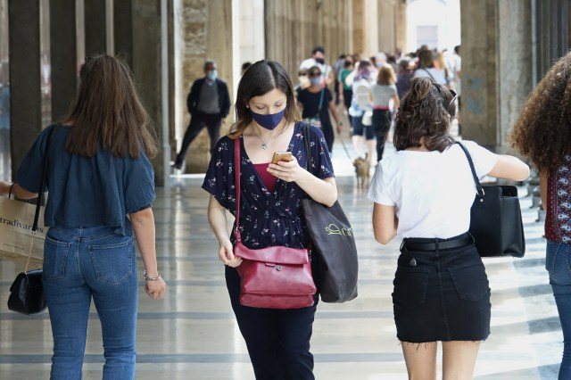 Woman wearing face mask walking on busy street checks phone