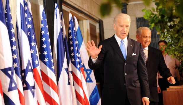 Biden waves next to an array of Israeli and US flags as Netanyahu walks behind him