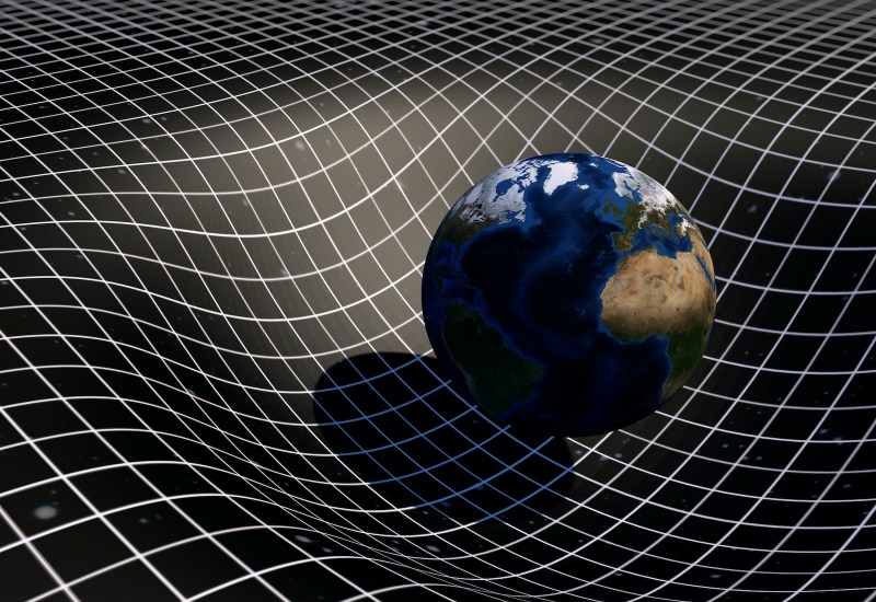 A model of the Earth showing it bend a grid representing spacetime.