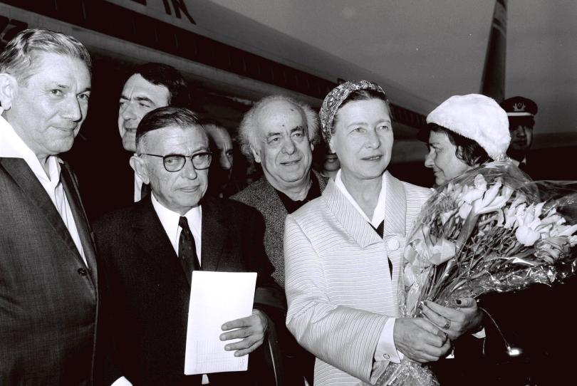 Jean Paul Sartre and Simone De Beauvoir surrounded by people in front of a plane.