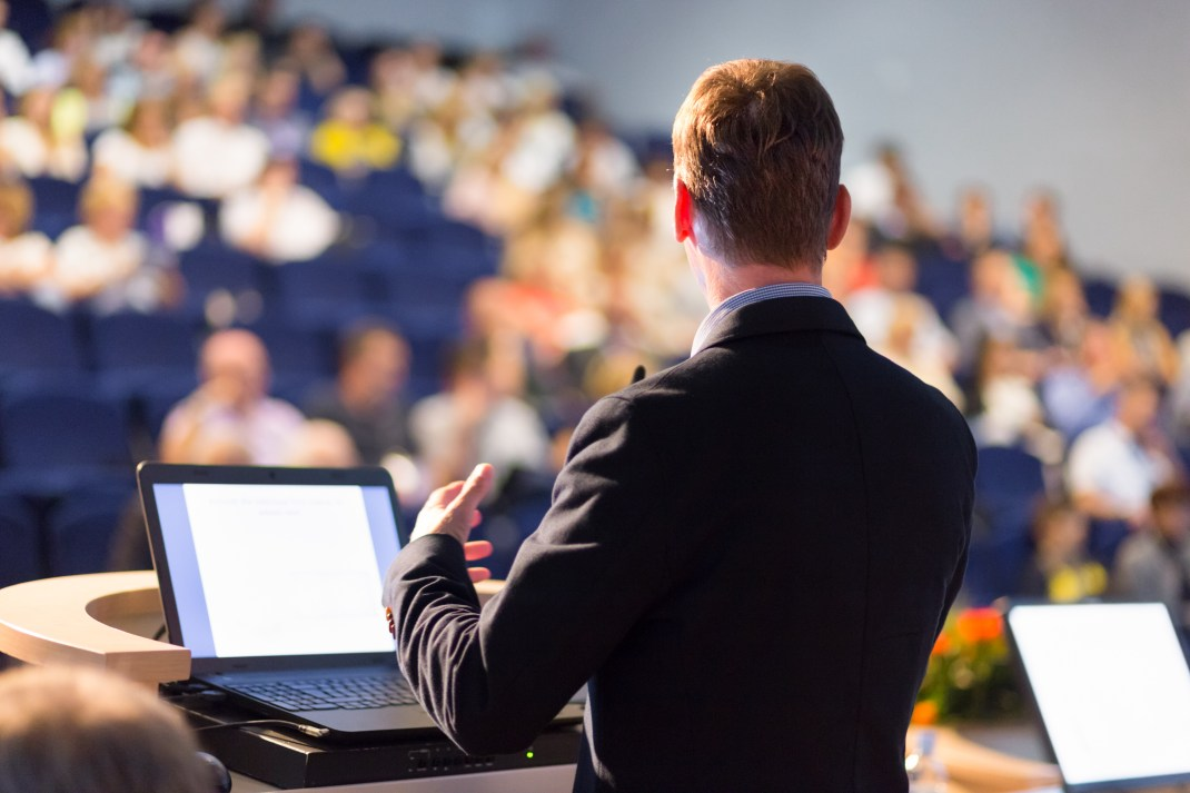 A man speaking before a crowded lecture theatre.