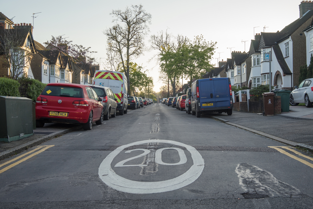 Suburban road with a 20mph speed limit sign painted on the tarmac.