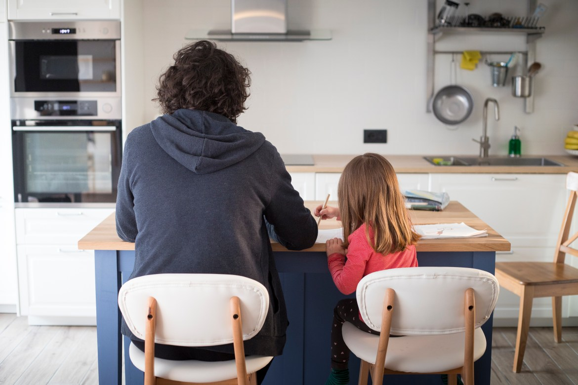 A man helps his daughter with schoolwork at the kitchen table.