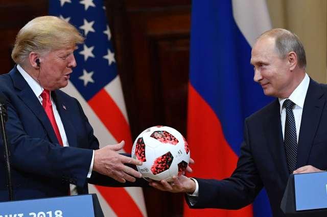 Russia's President Vladimir Putin offers a 2018 football World Cup ball to US President Donald Trump.