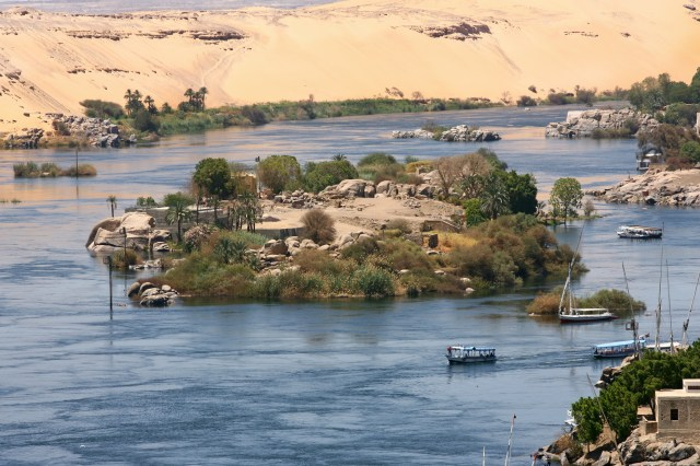 Island on the River Nile with palm trees and boats.
