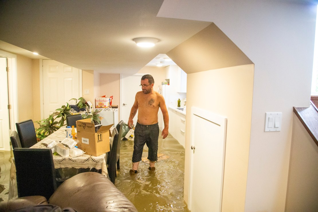 A man stands in shin-deep water in an apartment.