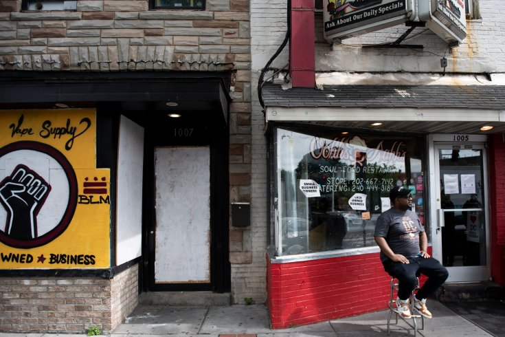 Chef Oji Abbot sits outside his restaurant and another Black-owned business, both of which feature anti-racism messaging