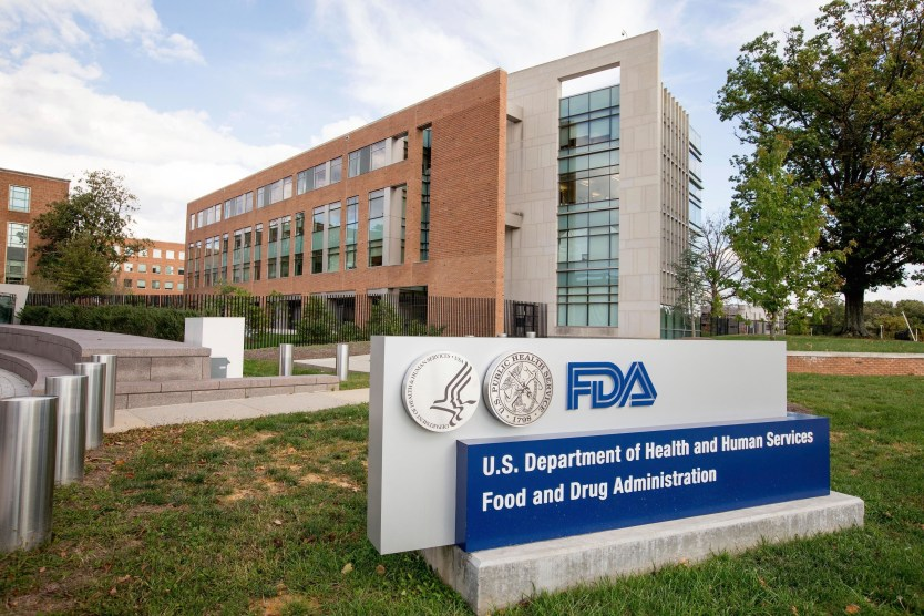 A sign showing the FDA logo with the FDA headquarters in the background.
