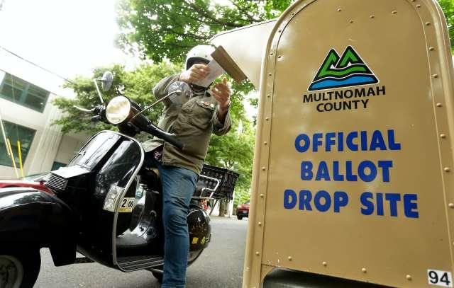 A motorcyclist puts a ballot in a drop box.