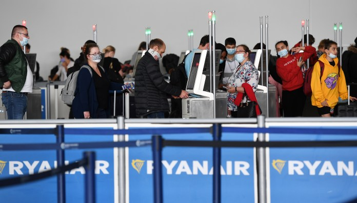 People wearing masks at a Ryanair desk.