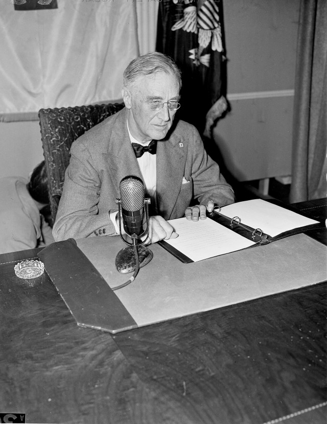 Franklin Roosevelt at a desk with a paper and a microphone