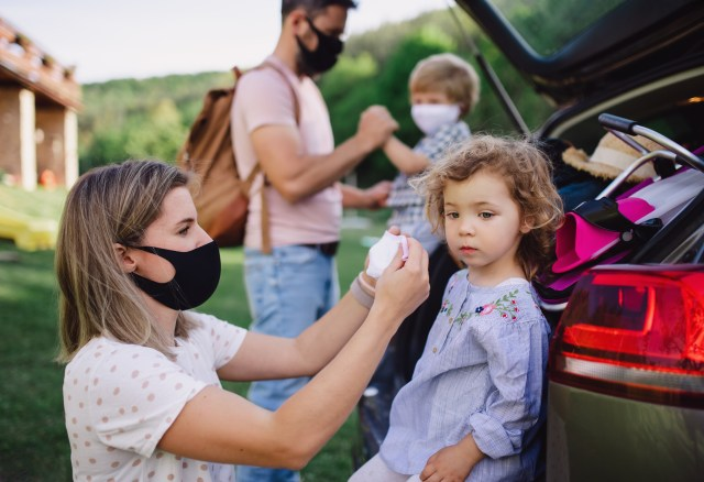 A family of four, putting on their masks while out in the countryside