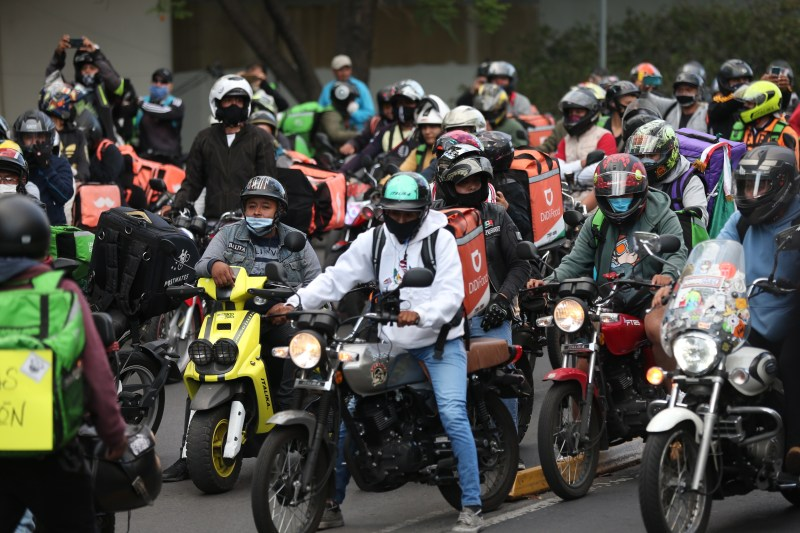 Large group of delivery drivers on scooters and motorbikes.