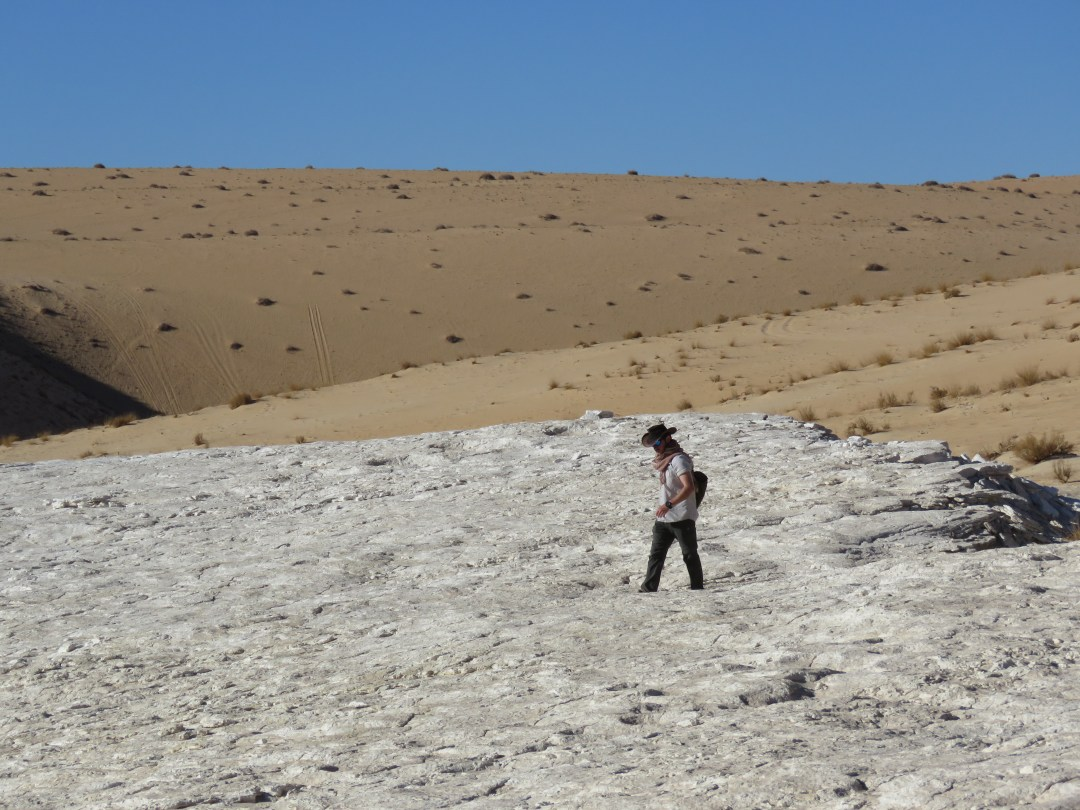 A man walks across a desert landscape. Earliest Evidence for Homo sapiens on Arabian Peninsula