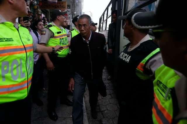 Police escort a man off a bus
