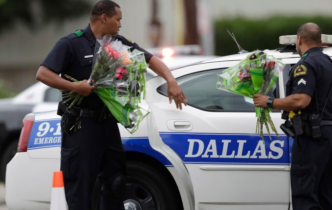 Two police officers standing in front of a police car hold flowers they were given.