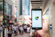 A hand holding up a mobile phone with the Google maps logo in a busy pedestrian area