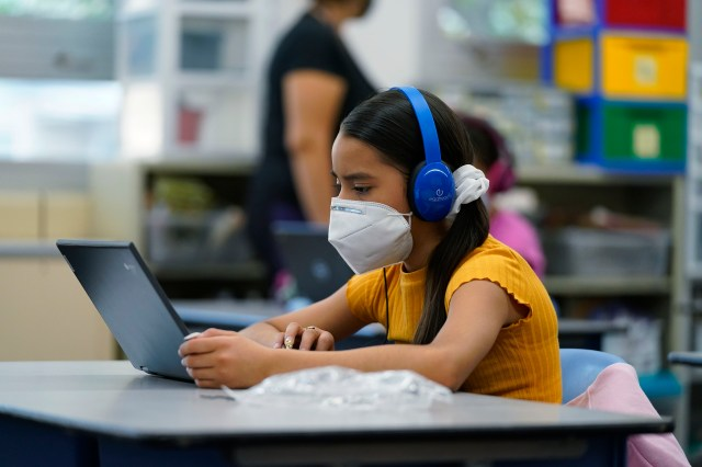A middle school girl wearing blue headphones and a face mask looks at her laptop.