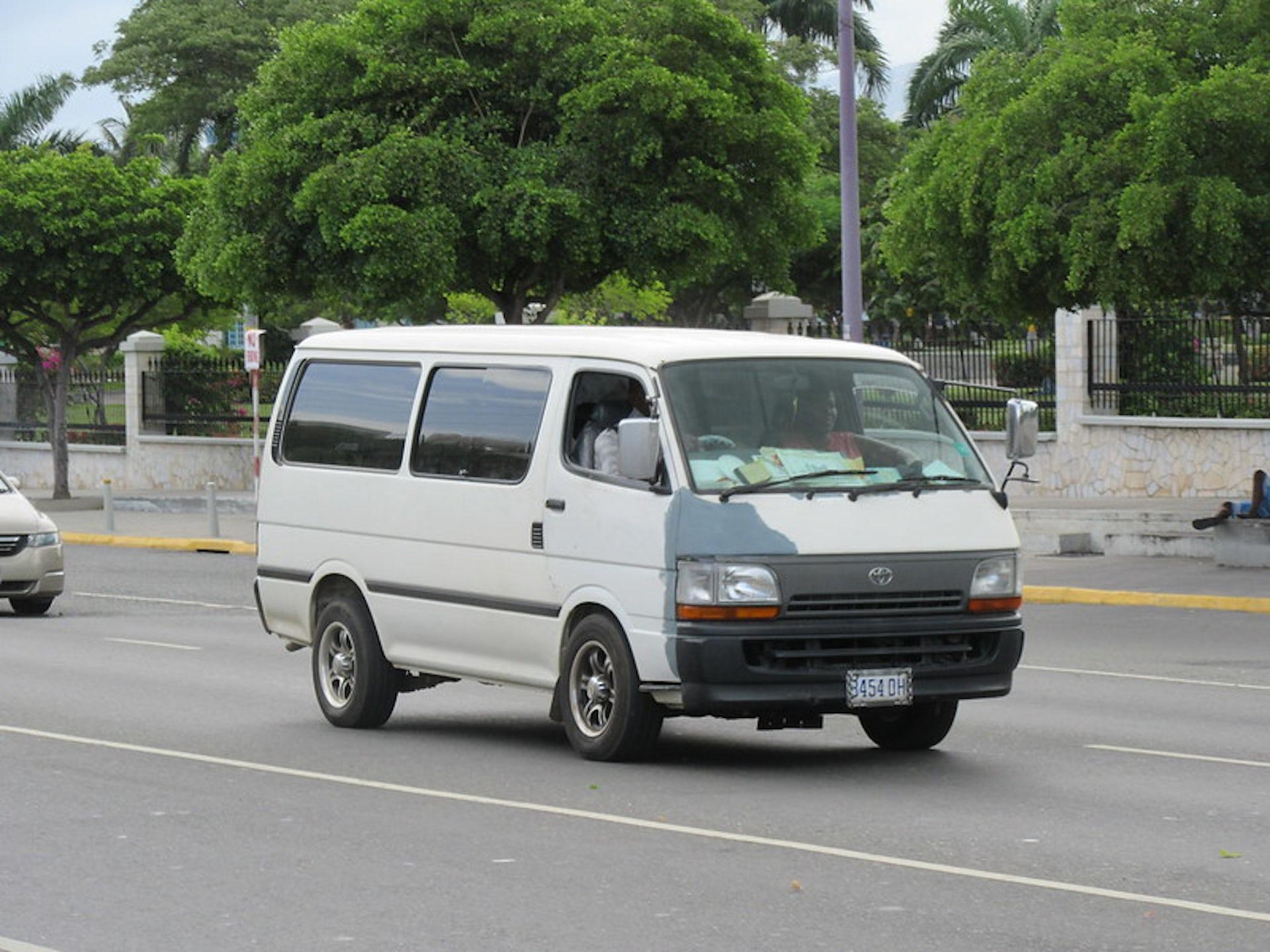 An old, white white Toyota minibus on a public road.