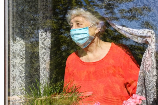 An elderly lady wearing a face mask stairs out of the window.