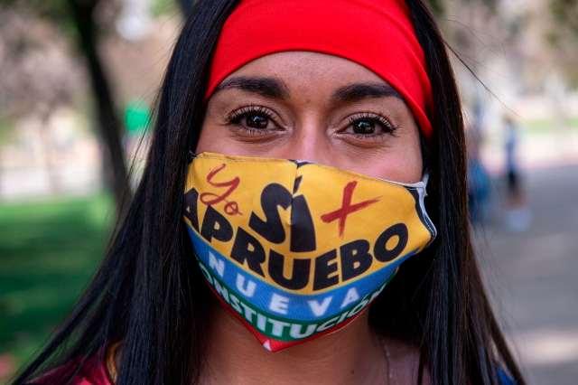 A woman in a face mask reading 'Sí apruebo.'