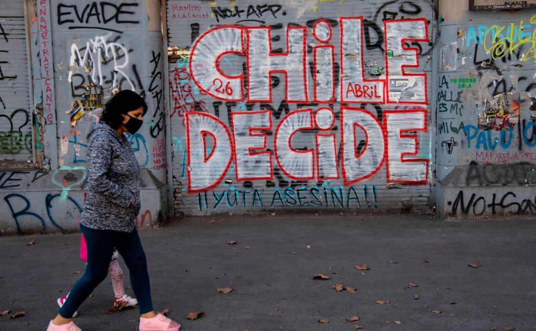 A woman in a face mask walks past graffiti reading 'Chile Decides'