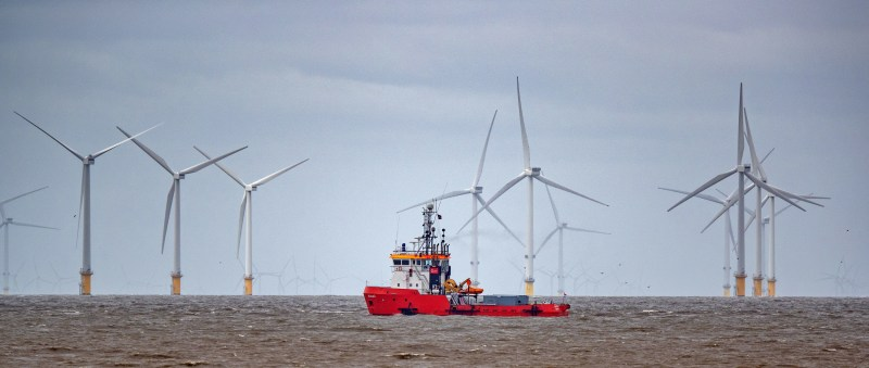 A red ship passes in front of wind turbines.