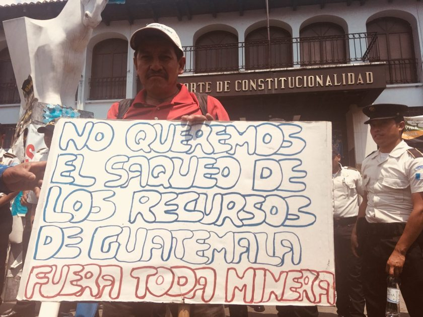 A man holds a sign in Spanish outside a courthouse that reads 'We do not want the looting of Guatemalan resources.'