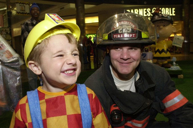 A boy dressed as a firefighter standing next to a real firefighter.