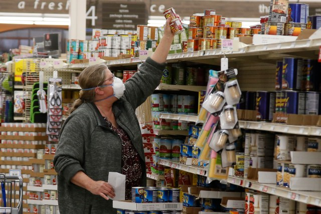 An older woman in a mask reaching to grab a can of food at a grocery store.