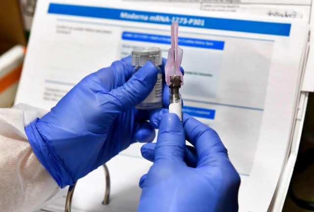 Two gloved hands holding a syringe and vaccine vial.