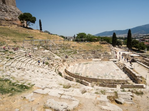 A photos of the ruins of the Theater of Dionysus showing rows upon rows of seats made of marble.