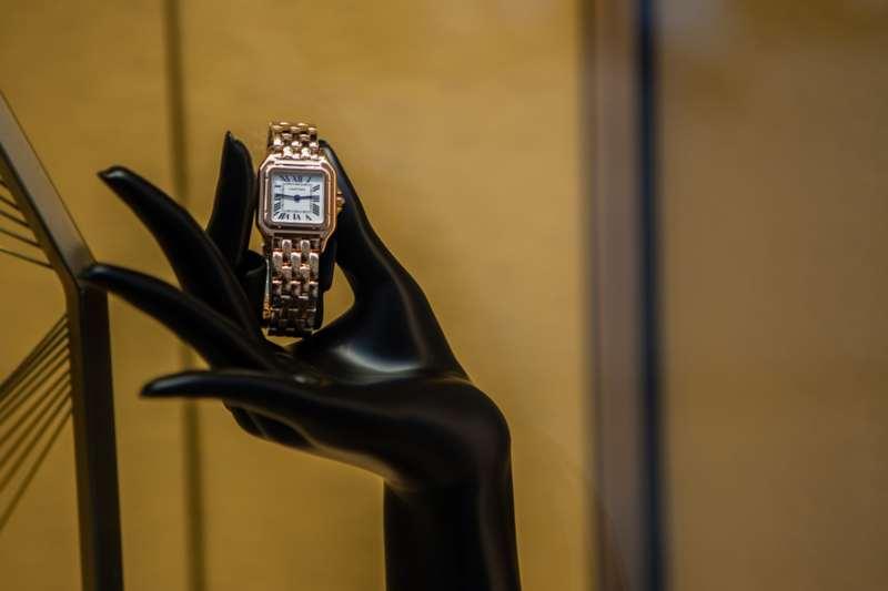 Hand holding up Cartier watch