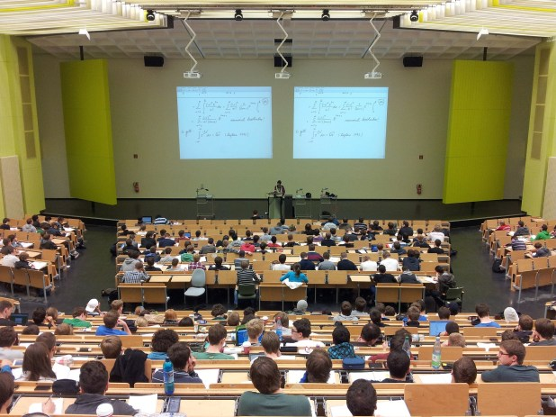 A lecture hall is seen filled with students and a professor at a podium.