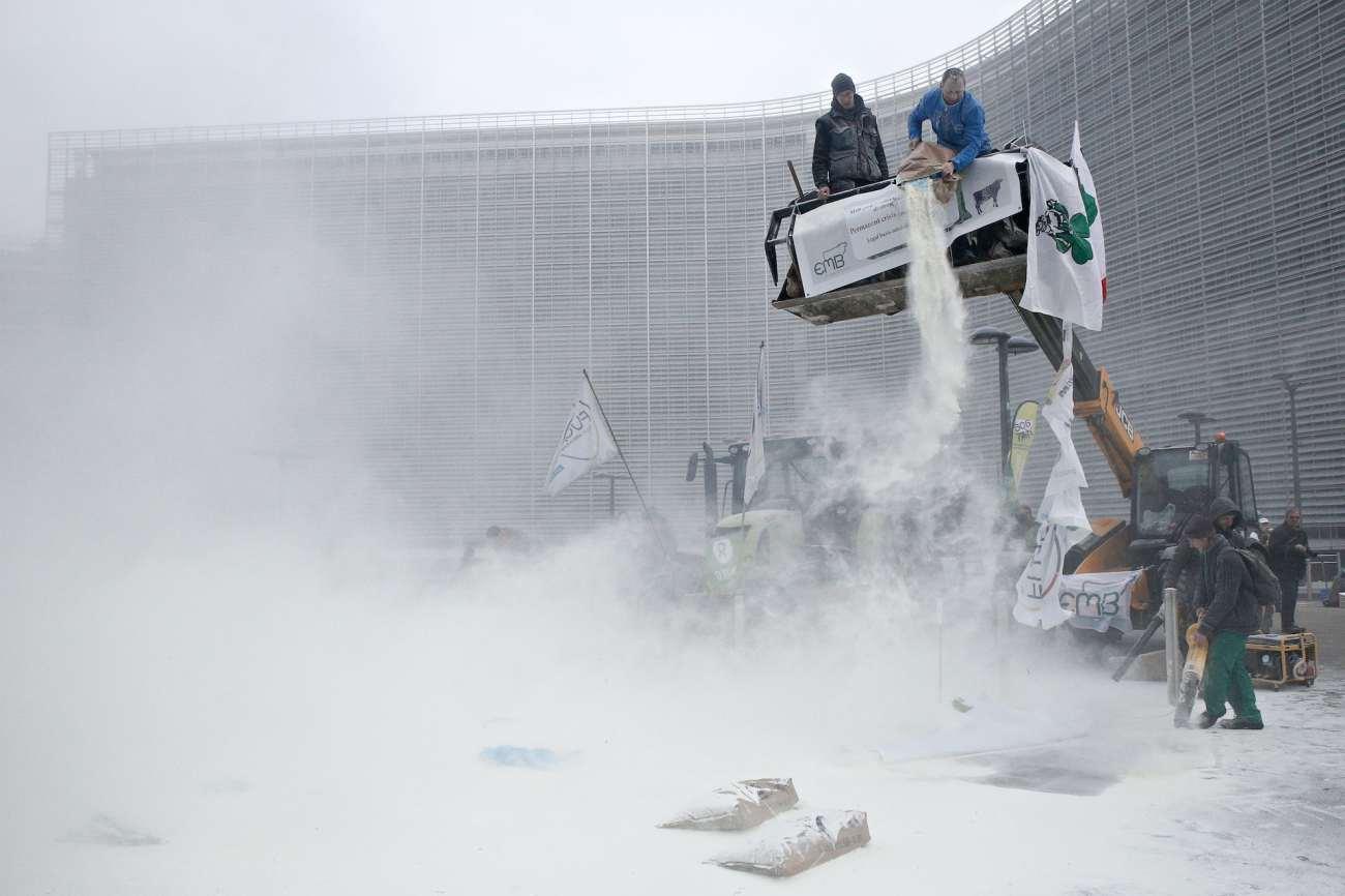 Gli agricoltori in protesta scaricano il latte in polvere da una piattaforma fuori dal Parlamento europeo.