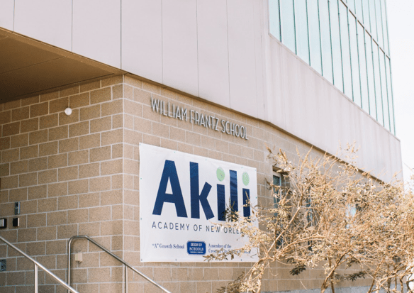 A sign saying Akili Academy on a beige brick building