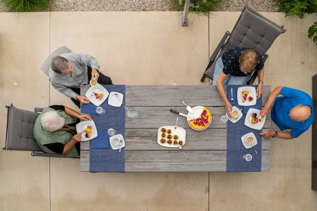 Two couples sit at opposite ends of a table outside while eating a meal.