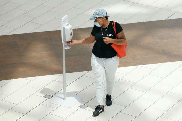 A woman wearing a mask using a hand sanitizer dispenser.