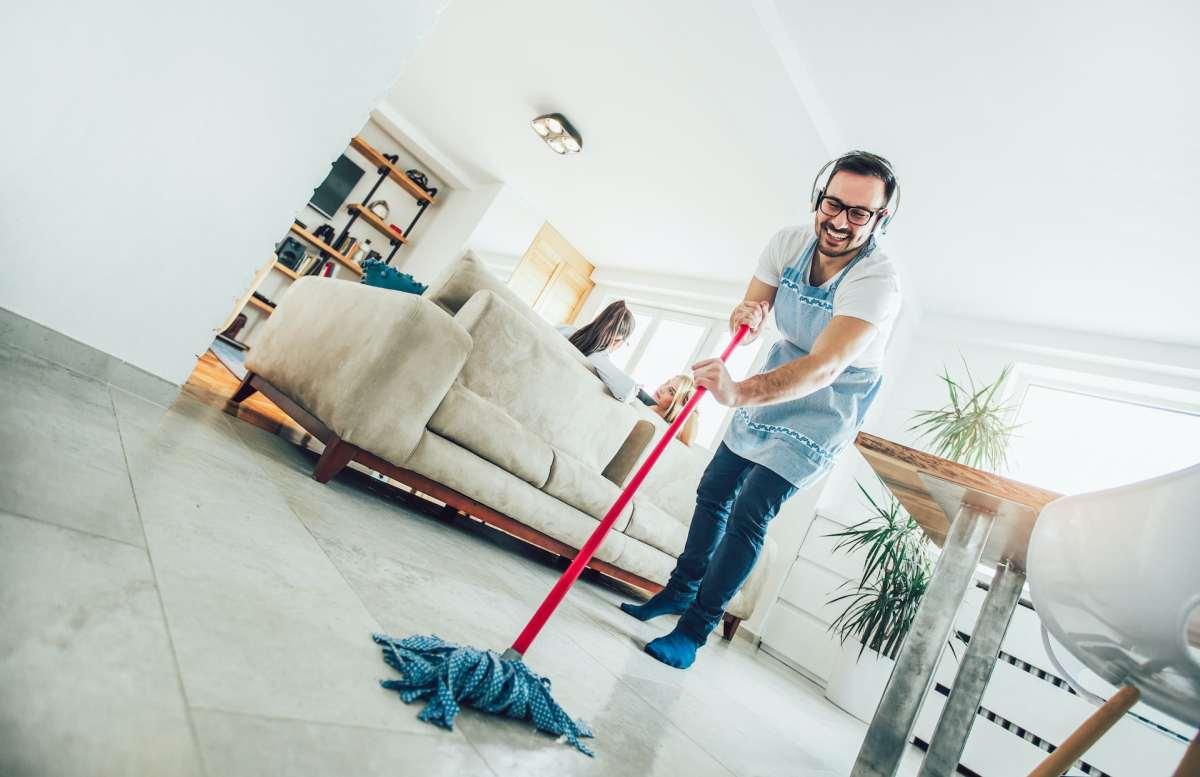 Un hombre con mandil fregando el suelo de una casa.