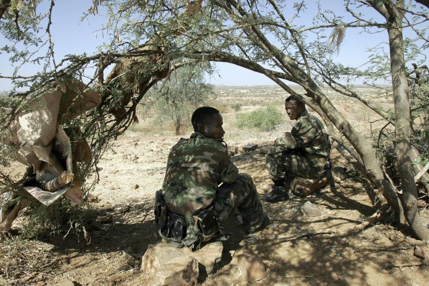 Two soldiers sit in the patchy shade of a tree. They are dressed in military camouflage uniforms with a vast plain of veld in the distance.