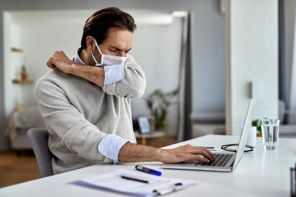 A man wearing a mask coughing