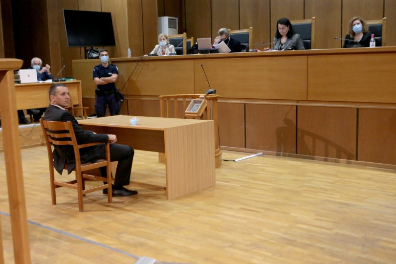 Ilias Kasidiaris, voormalig lid van Golden Dawn, zit in de rechtbank voor een rij rechters.