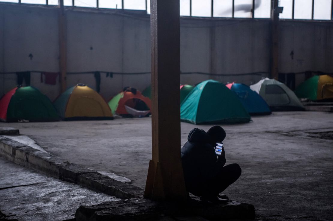 Silhouette of man crouching with mobile phone in hand with tents in the background