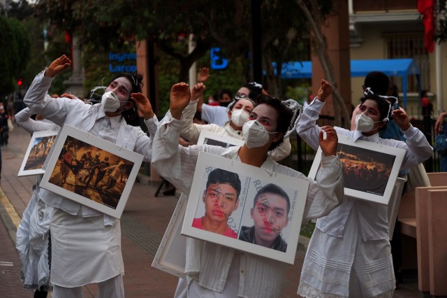 Women in white, carrying pictures of the protest marches where two young men were killed
