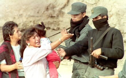 Peruvian police speak with a crying woman holding a baby
